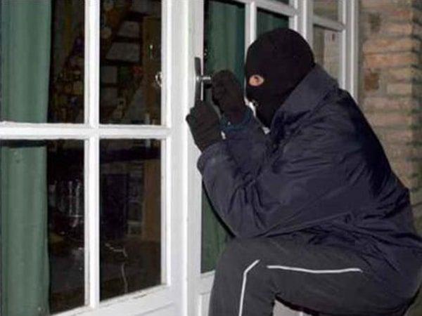 سارق در حال باز کردن قفل در منزل